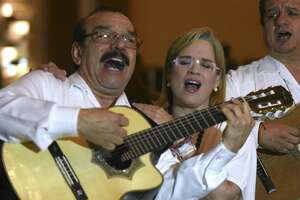 "Carmen Yulin Cruz Soto, mayor of San Juan, Puerto Rico, sings with Antonio Rodriguez, left, of the group ""El Trio Mio"" at the San Antonio Association of Hispanic Journalists annual gala on Aug. 11. Soto became internationally known for her criticism of President Trump after Hurricane Maria ravaged wide swaths of Puerto Rico, leaving many on the island without power for months on end."