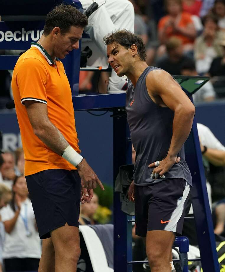Rafael Nadal (right) grimaces in pain as he talks with Juan Martin del Potro after withdrawing from their match. Photo: Kena Betancur / AFP / Getty Images