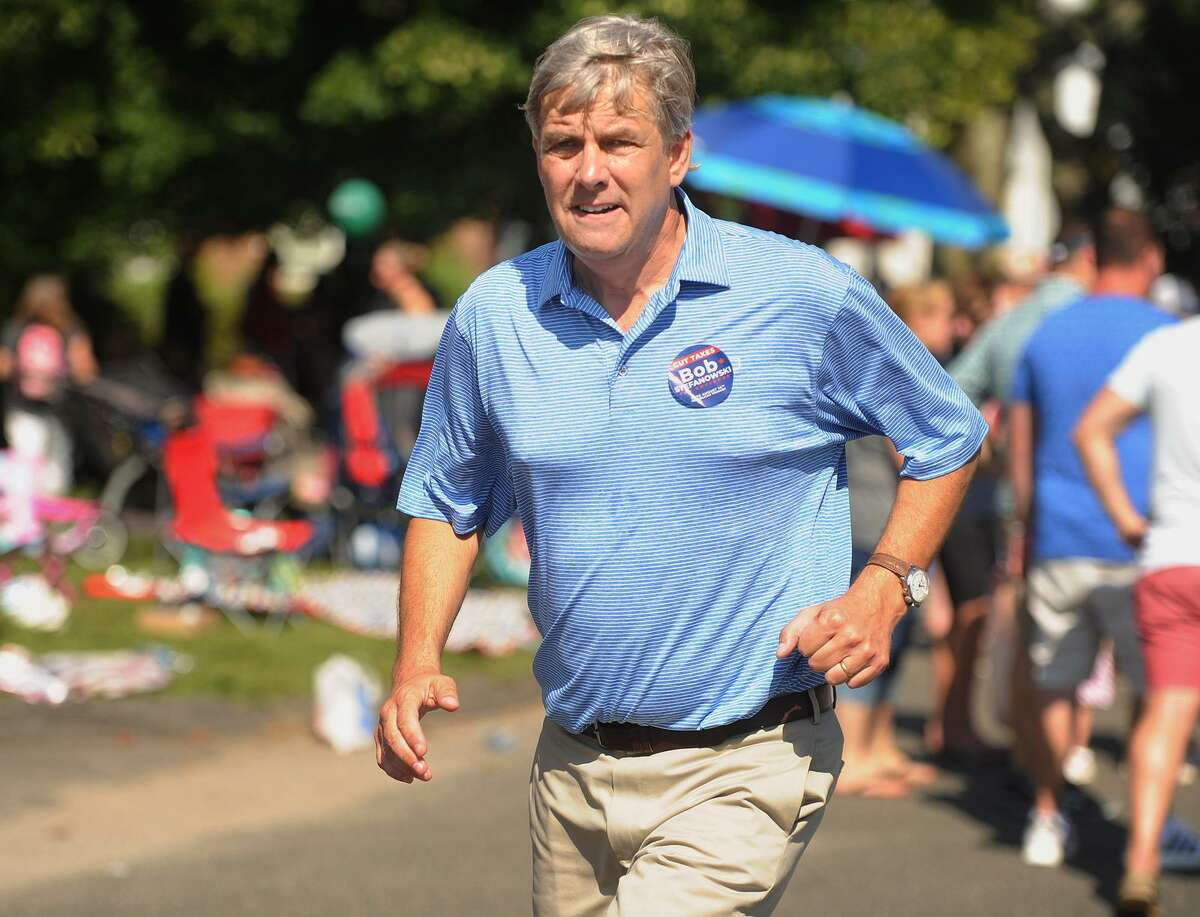 Republican candidate for governor Bob Stefanowski runs back and forth shaking hands during the Newtown Labor Day Parade on Main Street in Newtown last Monday.