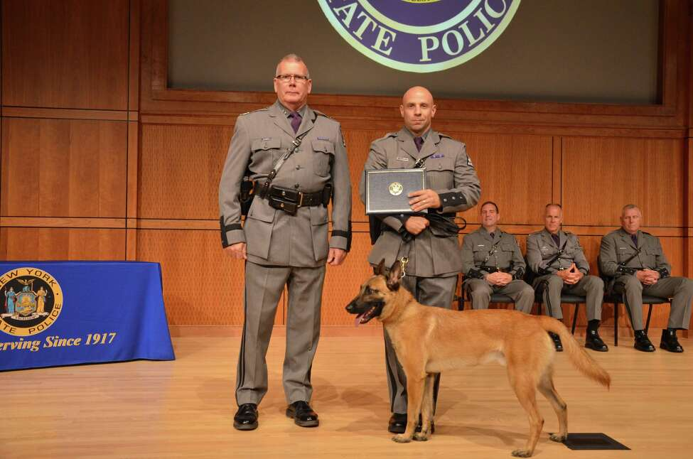 State Police Superintendent George P. Beach II, left, poses with Trooper Matthew P. Rufa and his new canine partner, Kinson, during a graduation ceremony on Aug. 7, 2018, in Albany, N.Y. The pair will serve Troop G in the Capital Region. Kinson is named after Cpl. Earl R. Wilkinson. The 28-year-old died on May 24, 1942, while on active duty with the Army Air Corps. His bomber crashed in a swamp near Houlton, Maine. He was a second lieutenant in the Air Corps.