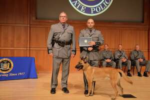 State Police Superintendent George P. Beach II, left, poses with Trooper Matthew P. Rufa and his new canine partner, Kinson, during a graduation ceremony on Aug. 7, 2018, in Albany, N.Y. The pair will serve Troop G in the Capital Region.   Kinson is named after Cpl. Earl R. Wilkinson. The 28-year-old died on May 24, 2942, while on active duty with the Army Air Corps. His bomber crashed in a swamp near Houlton, Maine. He was a second lieutenant in the Air Corps.