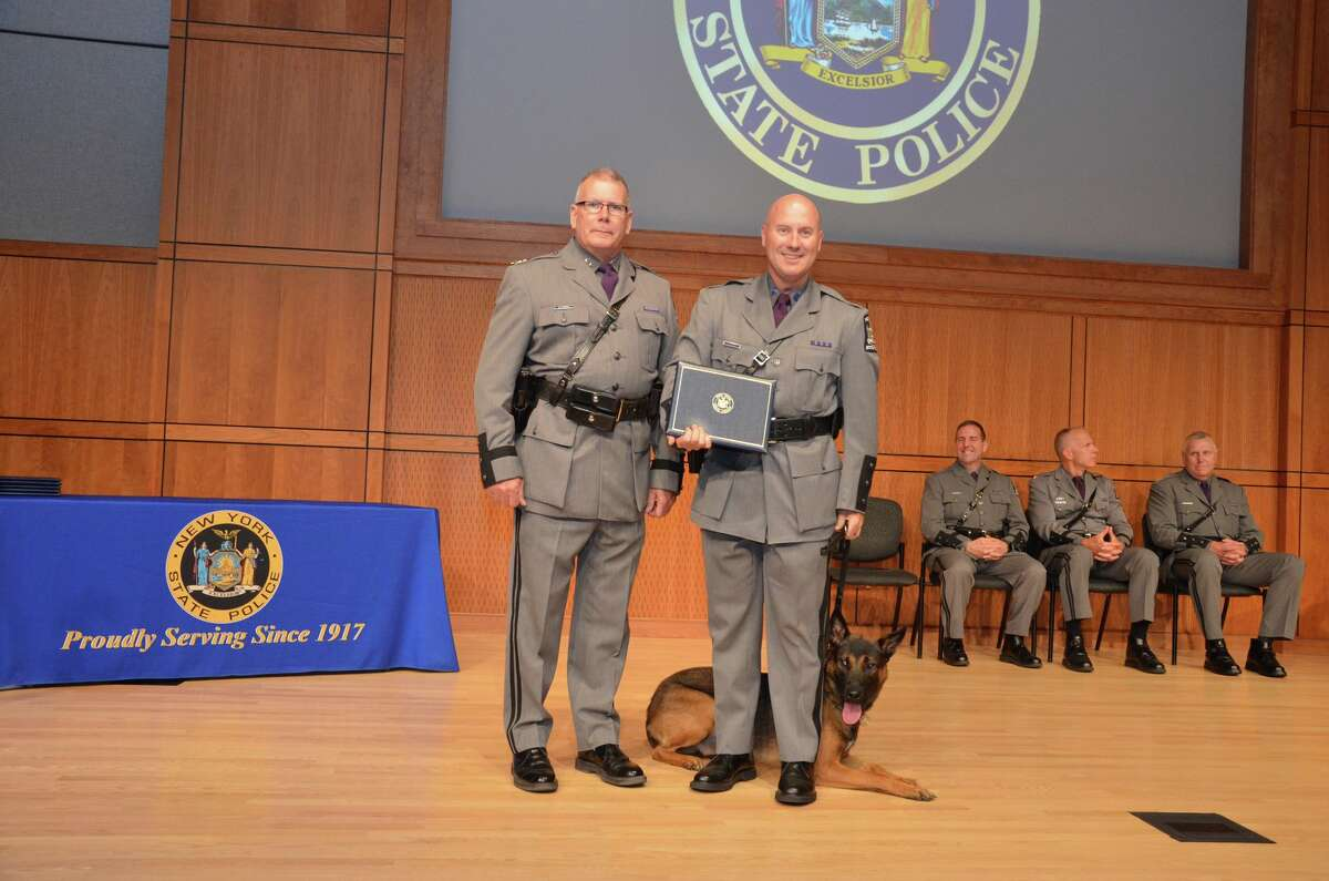 State Police Superintendent George P. Beach II, left, poses with Trooper Jason A. Miller and his new canine partner, Baker, during a graduation ceremony on Aug. 7, 2018, in Albany, N.Y. The pair will serve Troop G in the Capital Region. Baker is named after Cpl. Leroy John Baker. The 33-year-old was accidentally electrocuted by a downed wire at a crash site on Aug. 24, 1930. Baker was the first trooper on the scene of a car crash that had snapped a utility police on Johnstown Road in Caroga Lake, Fulton County. The corporal was trying to remove the pole from the highway when he touched a wire carrying 2,300 volts. He had served during World War I as a Maine and served the State Police for nine years.
