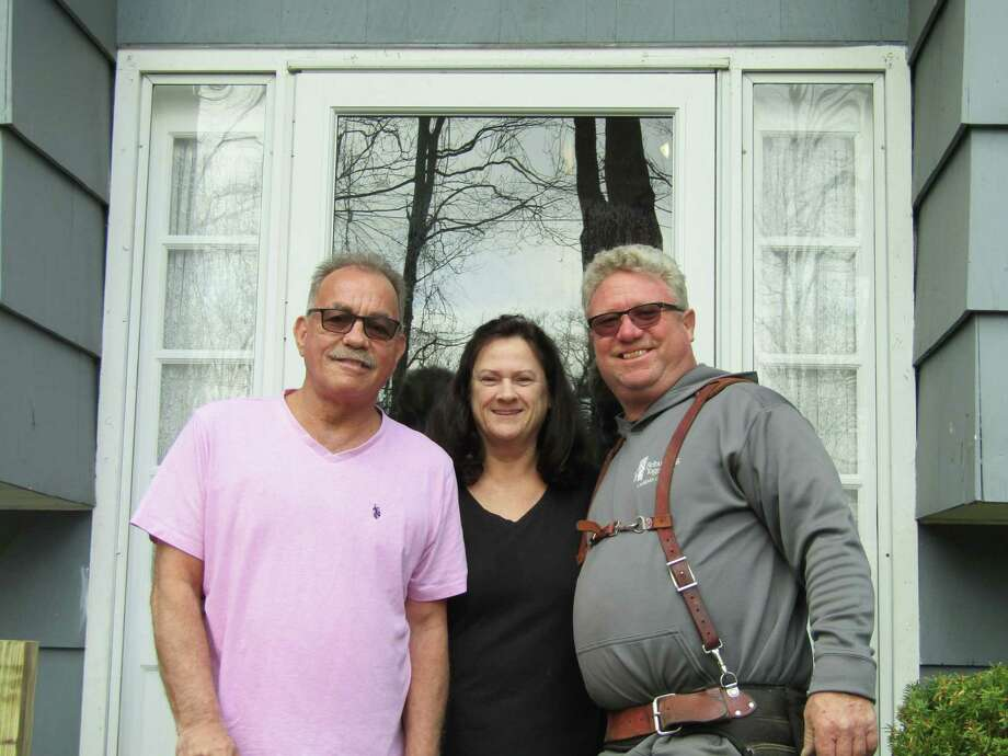 George and Karen Zigmantanis, center and left, are joined by Michael Boges, chairman of Rebuilding Together of Litchfield County. Photo: Contributed Photo /