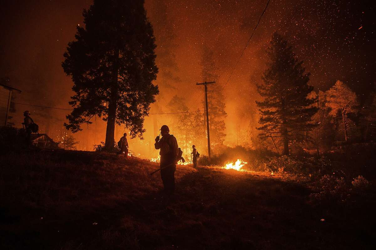 Firefighters monitor a backfire while battling the Delta Fire in the Shasta-Trinity National Forest.