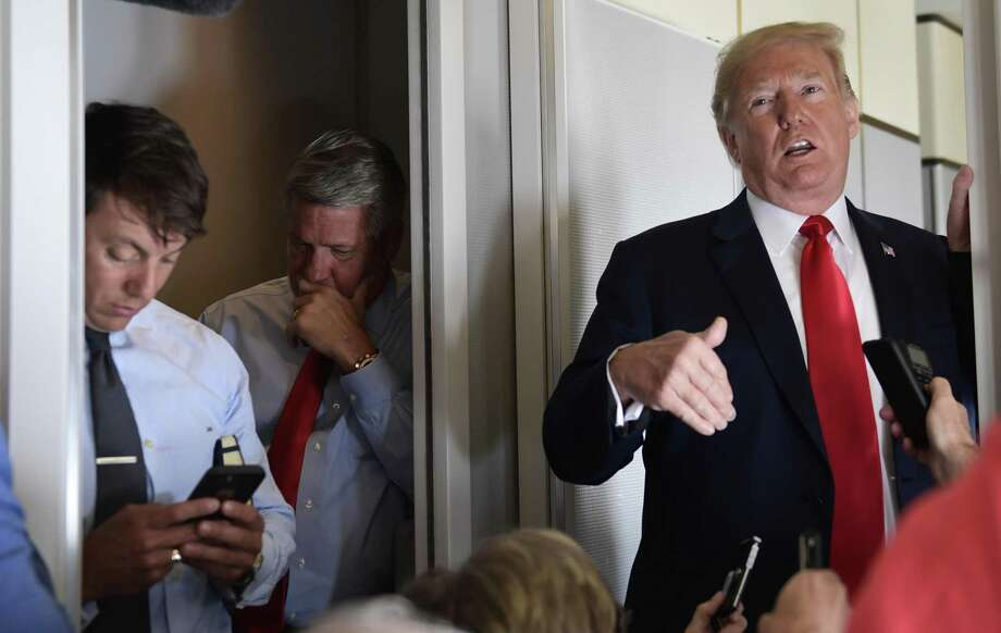 White House Deputy Press Secretary Hogan Gidley, left, and White House Deputy Chief of Staff for Communications, Bill Shine, center, listen as President Donald Trump talks to reporters while in flight from Billings, Mont., to Fargo, N.D., Friday, Sept. 7, 2018. (AP Photo/Susan Walsh) Photo: Susan Walsh /Associated Press / Copyright 2018 The Associated Press. All rights reserved.