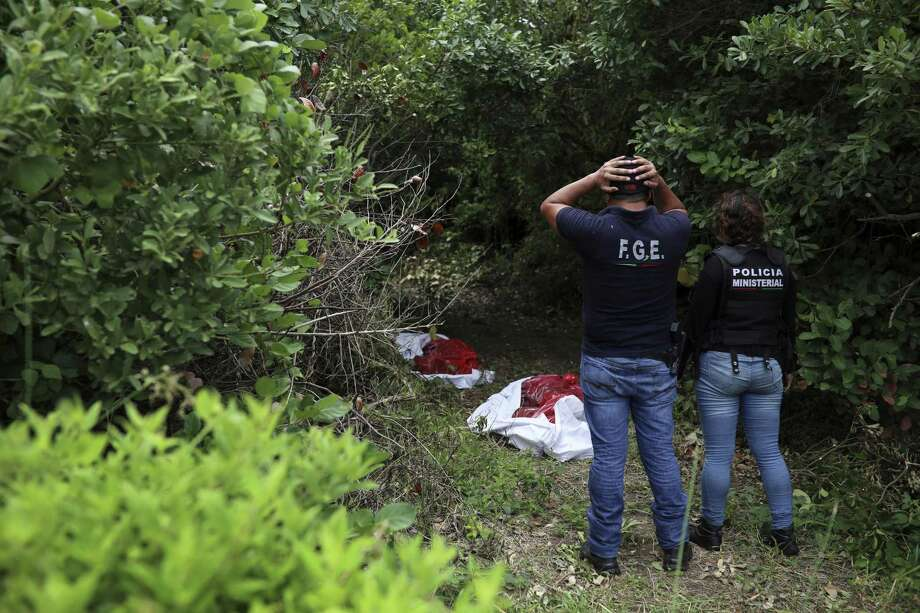 Investigators look at human remains placed in evidence bags, dug from a clandestine grave site in Arbolillo, Veracruz state, Mexico, Friday, Sept. 7, 2018. One day after authorities in the Mexican state of Veracruz announced the discovery of at least 166 skulls in mass graves, journalists who arrived at the site Friday discovered it was the same location where authorities said they had found 47 bodies the previous year. (AP Photo/Felix Marquez) Photo: Felix Márquez /Associated Press / Copyright 2018 The Associated Press. All rights reserved.