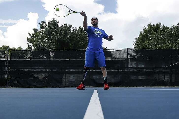 Jeff Bourns returns a ball at Bay Area Racquet Club in Houston. Bourns, an amputee, holds a top 5 world rank in adaptive tennis and pioneered ambulatory adaptive tennis with a tournament in the United States.