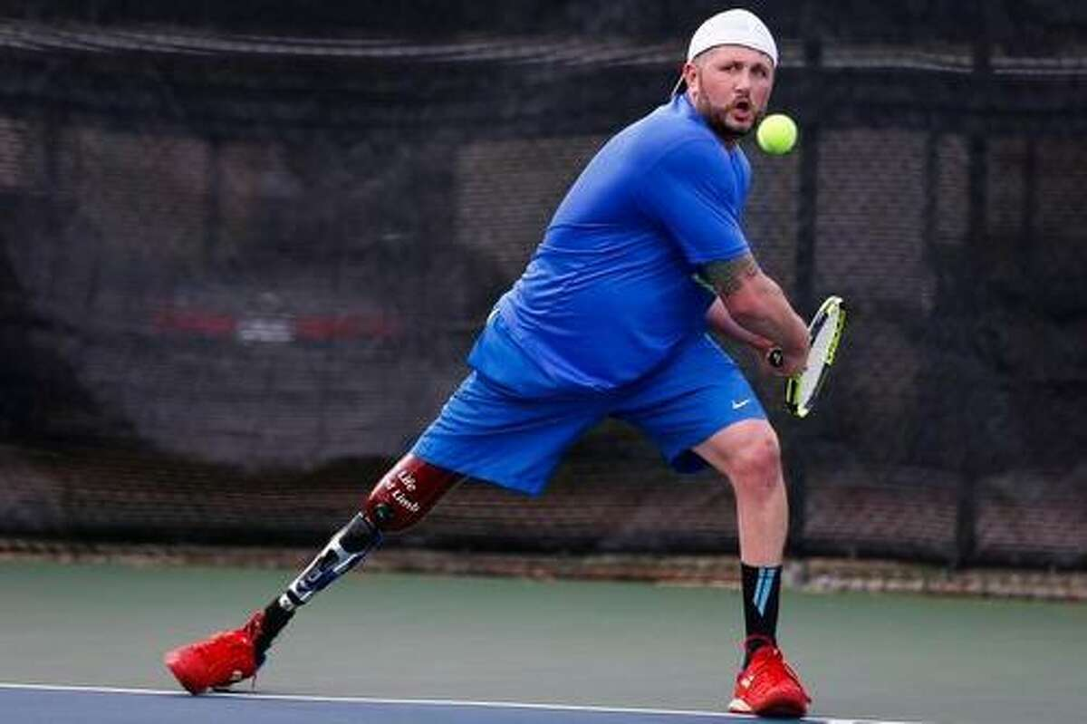 Ambulatory adaptive tennis pro Jeff Bourns sets up for a backhand at Bay Area Racquet Club in Houston. Bourns' leg was amputated as the result of a congenital birth defect; he was born without his right tibia.