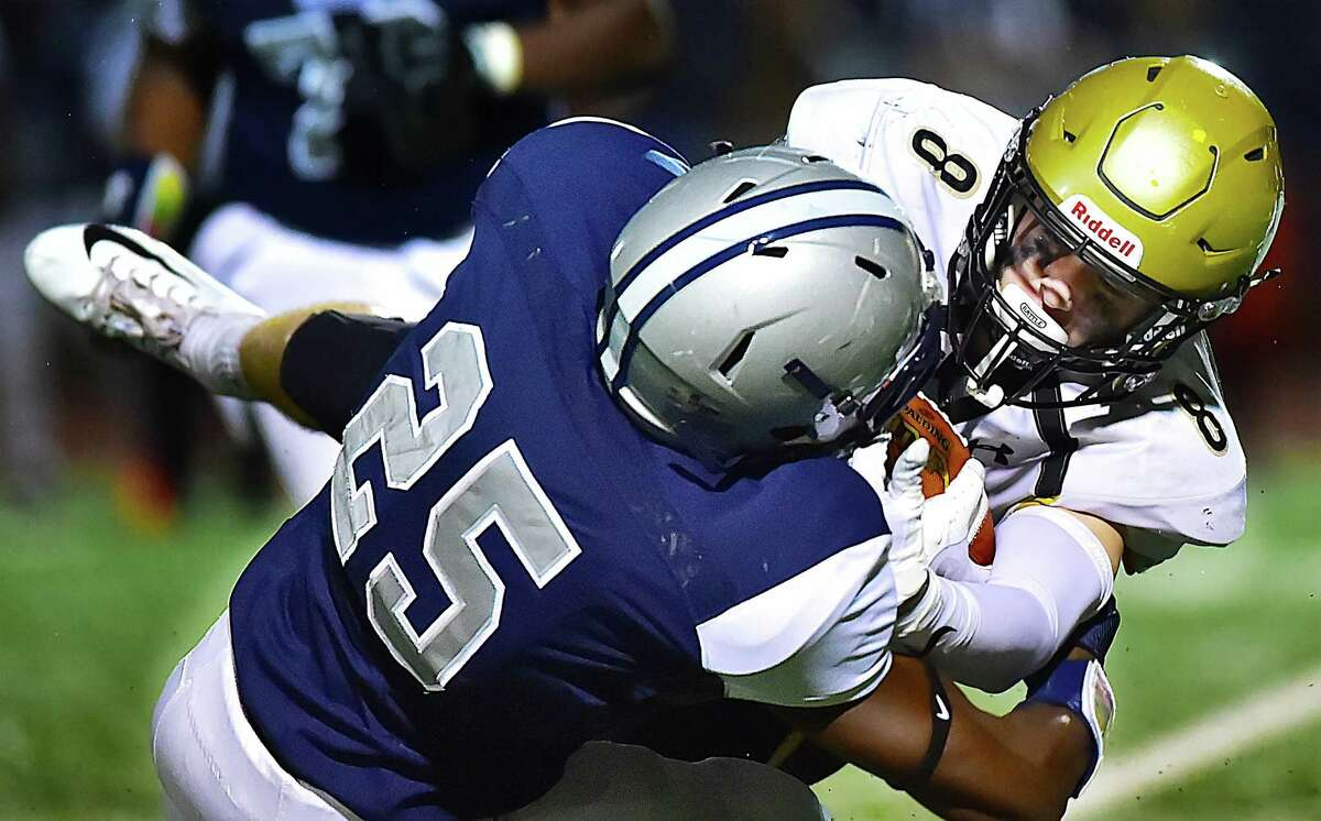 Hand's Ian Butler is tackled by Hillhouse defensive back Treronn Bryant during their game on Friday in New Haven.