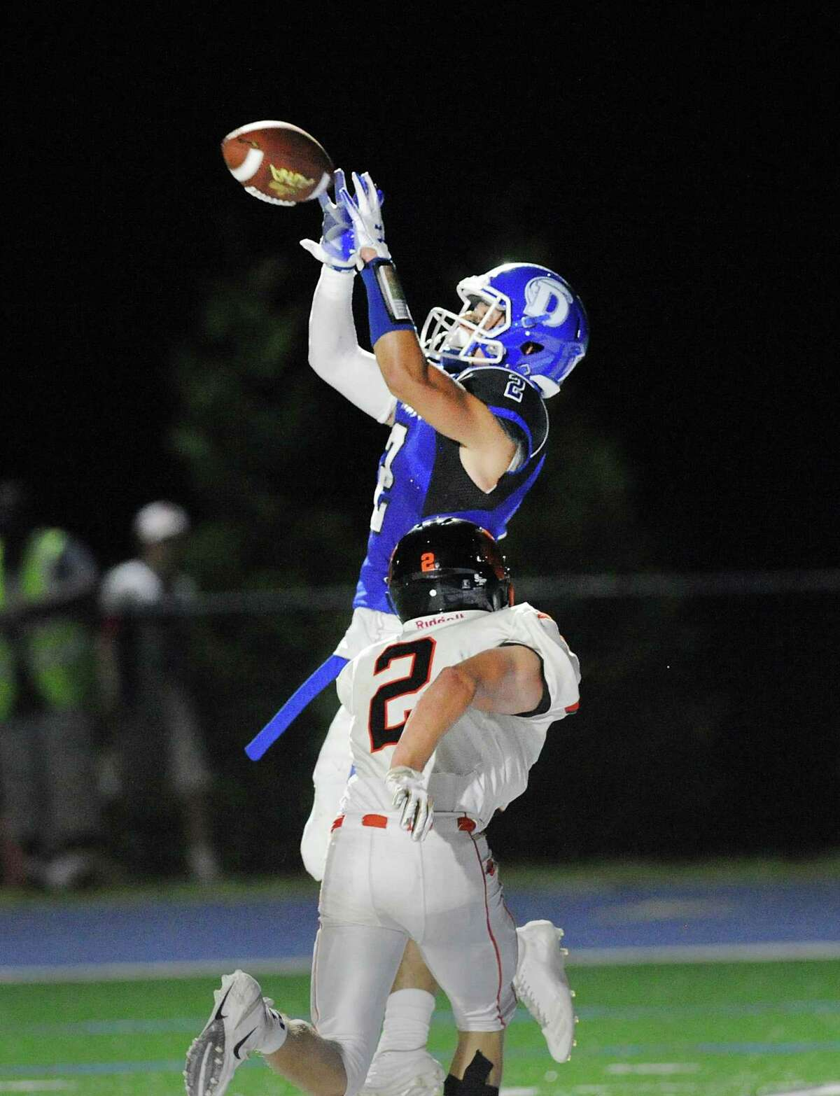 Darien receiver Will Rolapp jumps over Ridgefield defender Evan Wein for a second- quarter touchdown reception from Cooper Hancock during the season opener for both teams Friday night in Darien. Go to www.stamford advocate.com for game story.