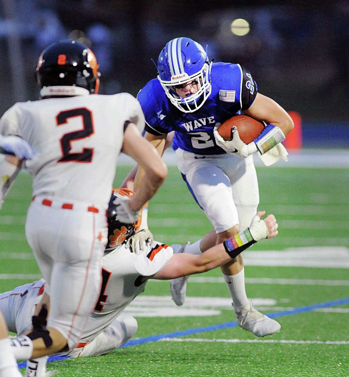 At right, Will Kirby, a Darien running back, breaks to the outside during the season opening high school football game between Darien High School and Ridgefield High School at Darien, Conn., Friday night, Sept. 7, 2018. Closing in for the tackle is Evan Wein (#2) of Ridgefield at left.