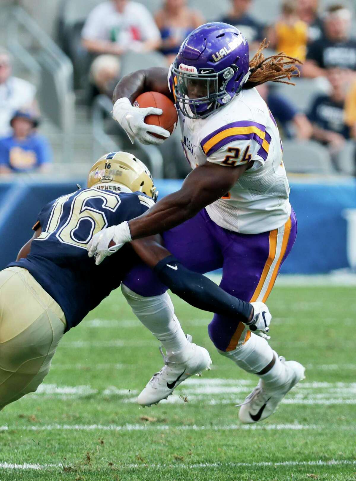 Albany running back Elijah Ibitokun-Hanks (24) tries to get past Pittsburgh defensive back Damarri Mathis (16) on a run in the first half of an NCAA football game, Saturday, Sept. 1, 2018, in Pittsburgh. (AP Photo/Keith Srakocic)