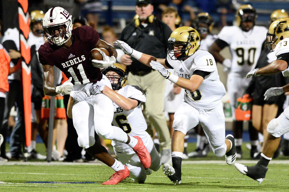 Lee's Loic Fouonji (11) tries to get away from Abilene's Tyler Simpson (16) and Ryan Cruz (18) Sept. 7, 2018, at Grande Communications Stadium. James Durbin/Reporter-Telegram Photo: James Durbin / ? 2018 Midland Reporter-Telegram. All Rights Reserved.