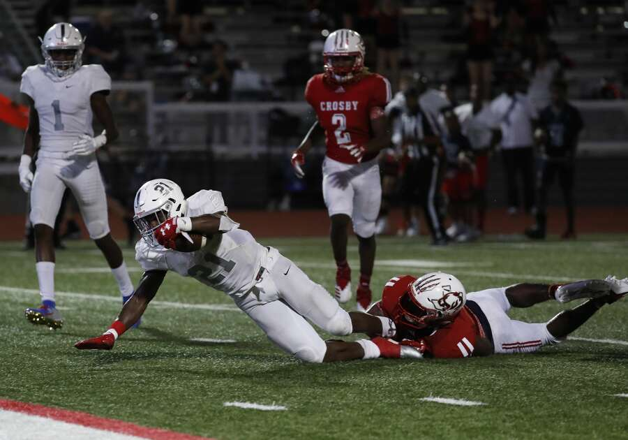 Manvel Ladarius Owens (21) reaches for the endzone as Crosby Terrance Wiley (9) grabs his feet during the second half of a high school football game at Cougar Stadium between Manvel and Crosby High Schools, Friday, September 7, 2018, in Crosby. Photo: Karen Warren/Staff Photographer