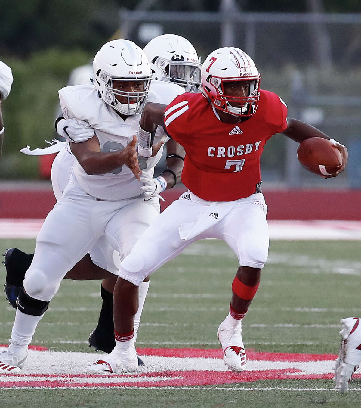Crosby quarterback Jaiden Howard (7) scrambles to gain yardage against the Manvel defense during the first half of a high school football game at Cougar Stadium between Manvel and Crosby High Schools, Friday, September 7, 2018, in Crosby.
