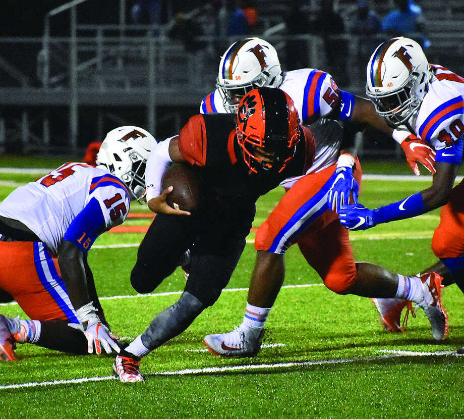 Edwardsville quarterback Kendall Abdur-Rahman tries to force his way past three East St. Louis defenders during the second quarter of Friday's Southwestern Conference game inside the District 7 Sports Complex. Photo: Matthew Kamp
