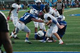 Clear Brook's Shane Porter (2) is wrestled down by Friendswood's Trey Mappe (14) and Ryan Helton (44) in a recent non-district football game.