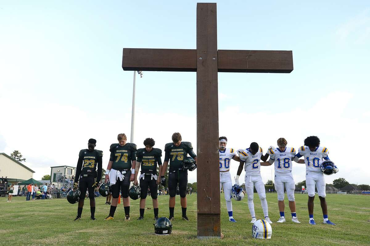 Captains for Legacy Christian Academy and Kelly Catholic pray at the cross in the south end zone before their game. Photo taken Friday 9/7/18 Ryan Pelham/The Enterprise