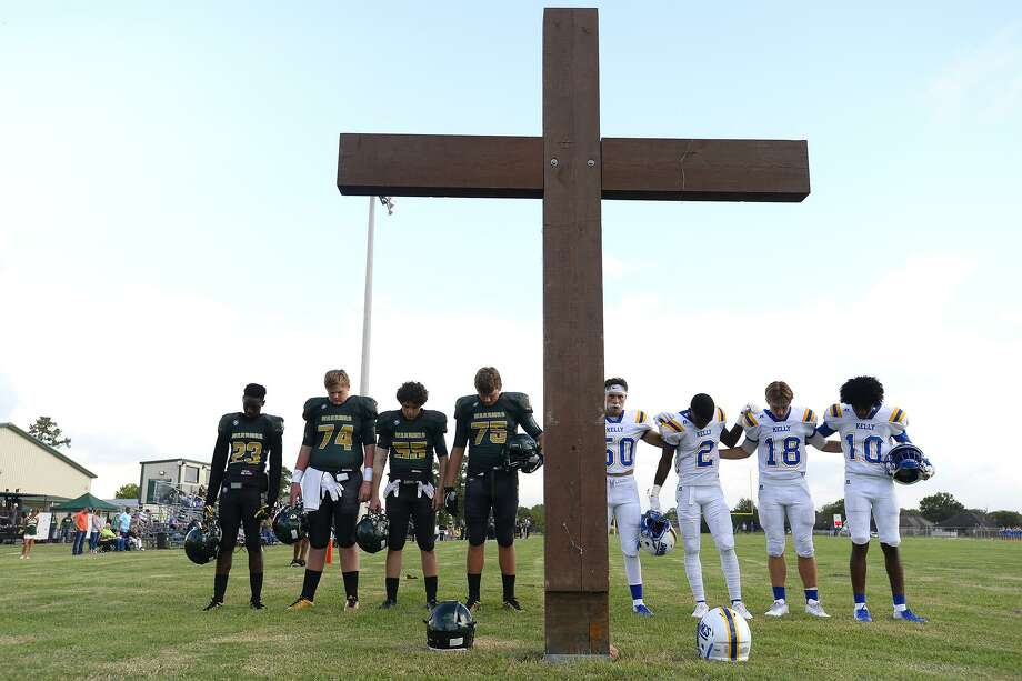 Captains for Legacy Christian Academy and Kelly Catholic pray at the cross in the south end zone before their game.   Photo taken Friday 9/7/18  Ryan Pelham/The Enterprise Photo: Ryan Pelham / The Enterprise / ©2018 The Beaumont Enterprise