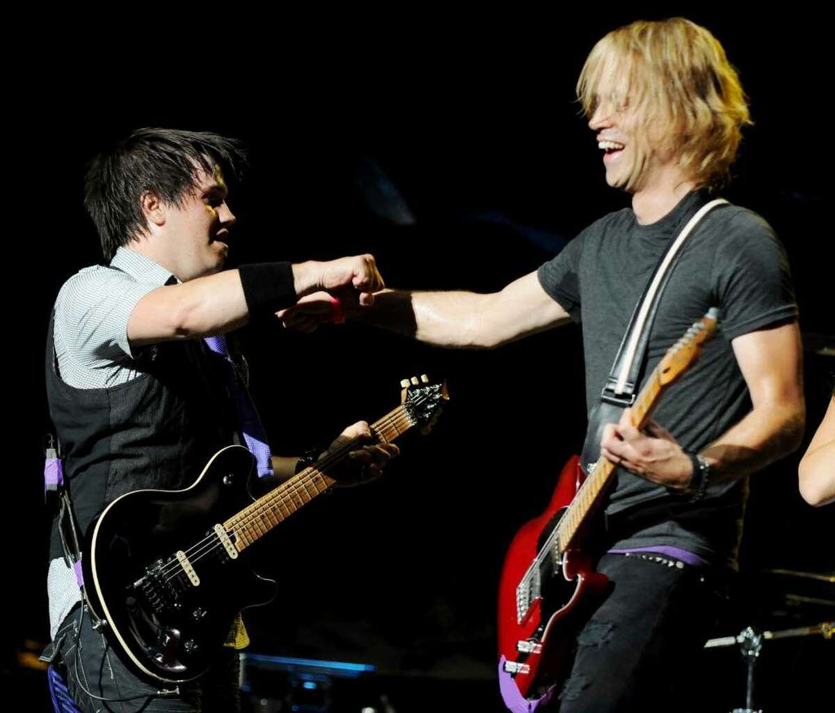 Lead guitarist Andrew Foster, left, and guitarist Mark Rose, right, of the local band Ten Year Vamp give eachother the fist pump as they perform on stage at SPAC, on Sunday, July 11, 2010, Saratoga Springs, NY. The group got a big break at the Saratoga Performing Arts Center, warming up for headliner Jon Bon Jovi. (Luanne M. Ferris / Times Union)