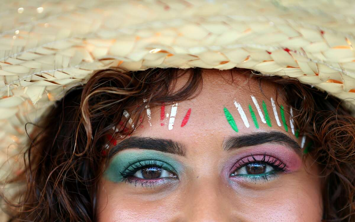White, green, and red paint color Viviana Gonzalez's forehead in support of the Mexico men's national team before they face Uruguay at NRG Stadium Friday, Sept. 7, 2018, in Houston.