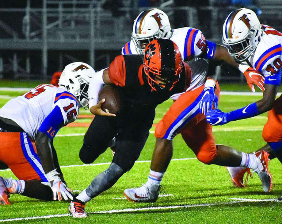 Edwardsville quarterback Kendall Abdur-Rahman (middle) tries to force his way past three East St. Louis defenders during the second quarter of Friday's Southwestern Conference game at the District 7 Sports Complex in Edwardsville. Photo: Matthew Kamp / Hearst Illinois