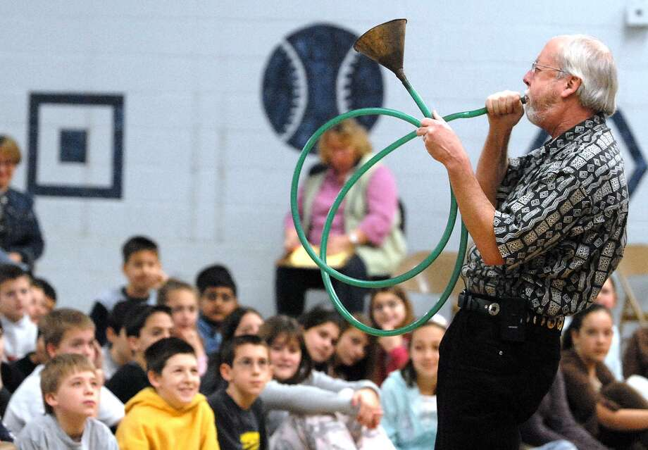 Ethnomusicologist Dennis Waring of Middletown plays on an improvised instrument made out of hosuehold scraps to a gym filled with fifth- and sixth-graders from the Elizabeth Shelton School. Photo: File Photo