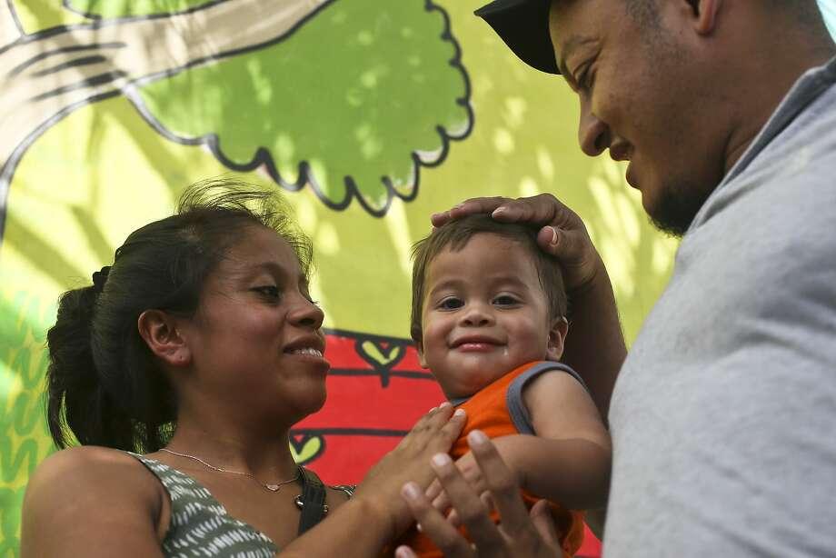 Adalicia Montecinos and Rolando Bueso Castillo hold their son Johan in Honduras in July after the family was reunited. Photo: Esteban Felix / Associated Press