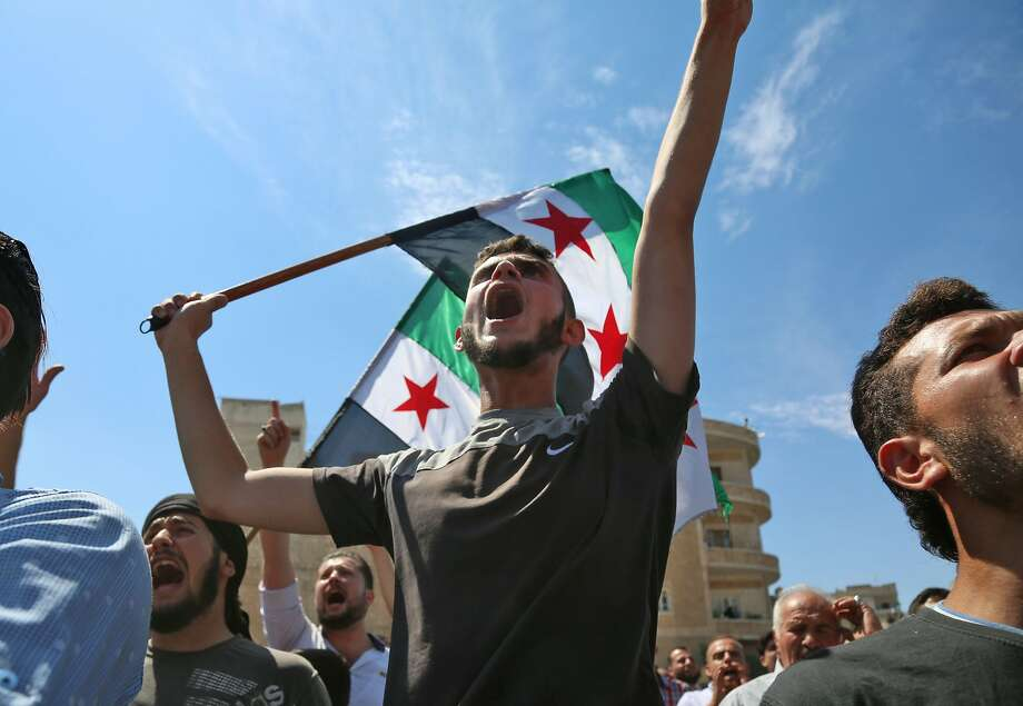 "TOPSHOT - Syrian protesters wave the flag of the opposition as they demonstrate against the regime and its ally Russia, in the rebel-held city of Idlib on September 7, 2018. - Damascus has every right to take back all its territory, Russian President Vladimir Putin told a summit on September 7 expected to decide the fate of Syria's last major rebel bastion Idlib. The legitimate Syrian government has a right and must eventually take under control all of its national territory,"" Putin told Iran's Hassan Rouhani and Turkish leader Recep Tayyip Erdogan at the summit. (Photo by Zein Al RIFAI / AFP)ZEIN AL RIFAI/AFP/Getty Images Photo: ZEIN AL RIFAI;Zein Al Rifai / AFP / Getty Images"