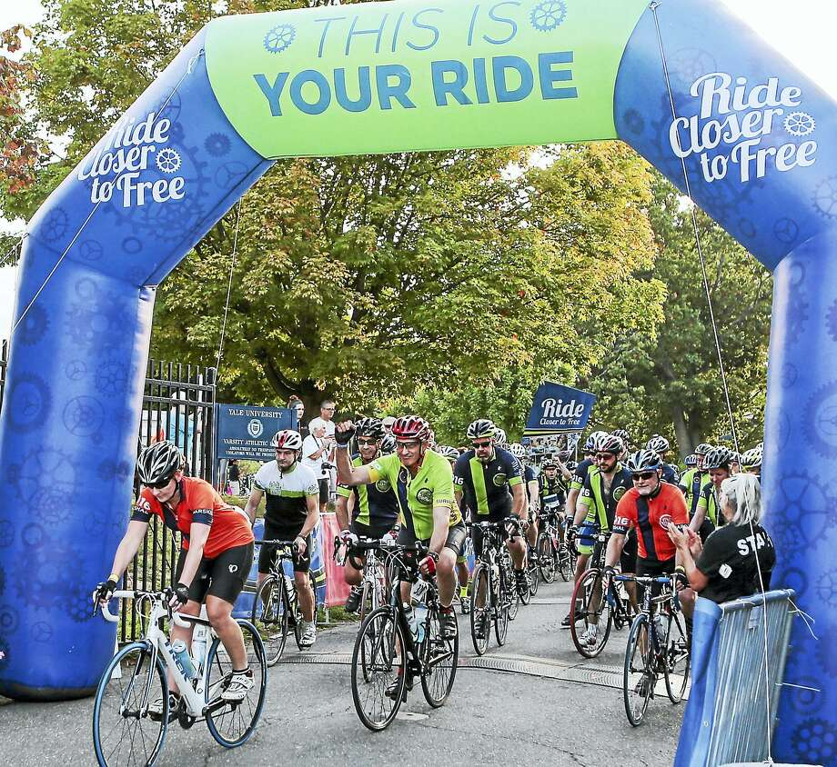 """Bicyclists pass under the arch to begin the Smilow Cancer Hospital's """"Closer to Free"""" ride in 2016. Photo: File / John Vanacore/New Haven Register`"""