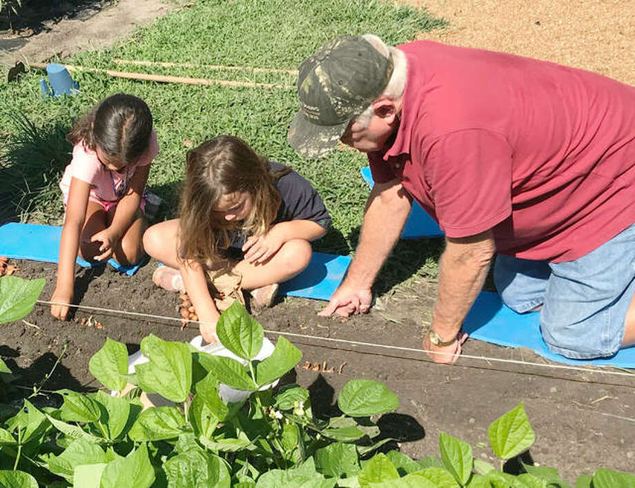 Bethalto Boys and Girls Club members Joslyn Springman and Piper Davis work with garden planner Gerald Eberhart to plant bulbs in the community garden created by United Methodist Church members. The garden was installed to teach the Bethalto club's youth members about gardening and the responsibility, and fun, that comes with it. Other adult volunteers who helped include Rose Bickmore, Bob Cleveland, Bob Crause, Whitney Eberhart, Ed Graveman, Janet Graveman, Vernon Hamel, Bill Pyatt, Mary Lou Stephenson, Janet Whalum, and Diane Winkler. Photo: For The Telegraph