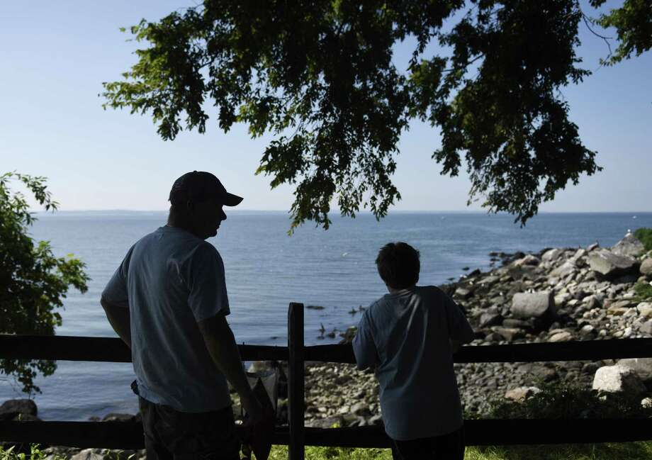 Island caretaker Mike Nickerson and his son Michael Jr., 10, overlook the shoreline filled with nesting birds on Great Captain's Island in the Long Island Sound off the coast of Greenwich, Conn. Wednesday, Aug. 15, 2018. Nickerson has been the island's caretaker for 16 years, living in the lighthouse and taking care of landscaping, cleanup and emergencies on the island. Photo: Tyler Sizemore / Hearst Connecticut Media / Greenwich Time