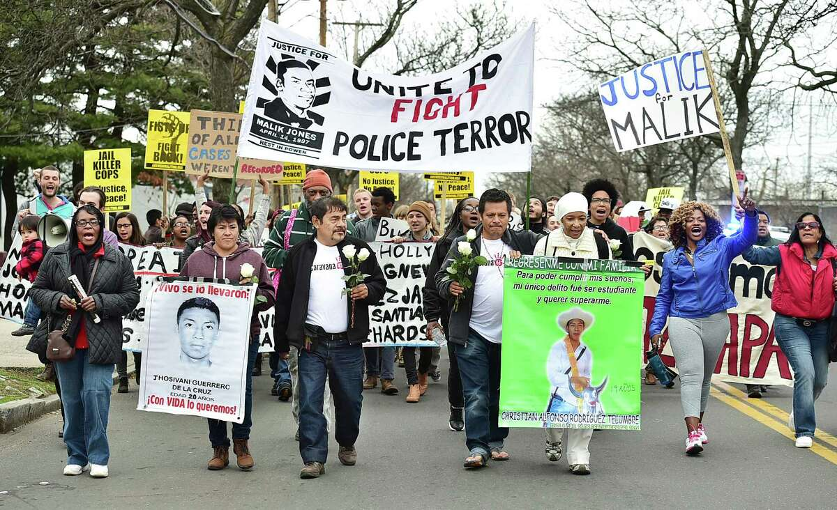 """Clemente Rodriguez Moreno, of Guerrero, Mexico, puts his arm around Emma Jones, mother of Malik Jones, as they lead marchers down Grand Avenue in the Fairhaven section of New Haven during a """"Rally Against Police Violence"""" in 2015."""