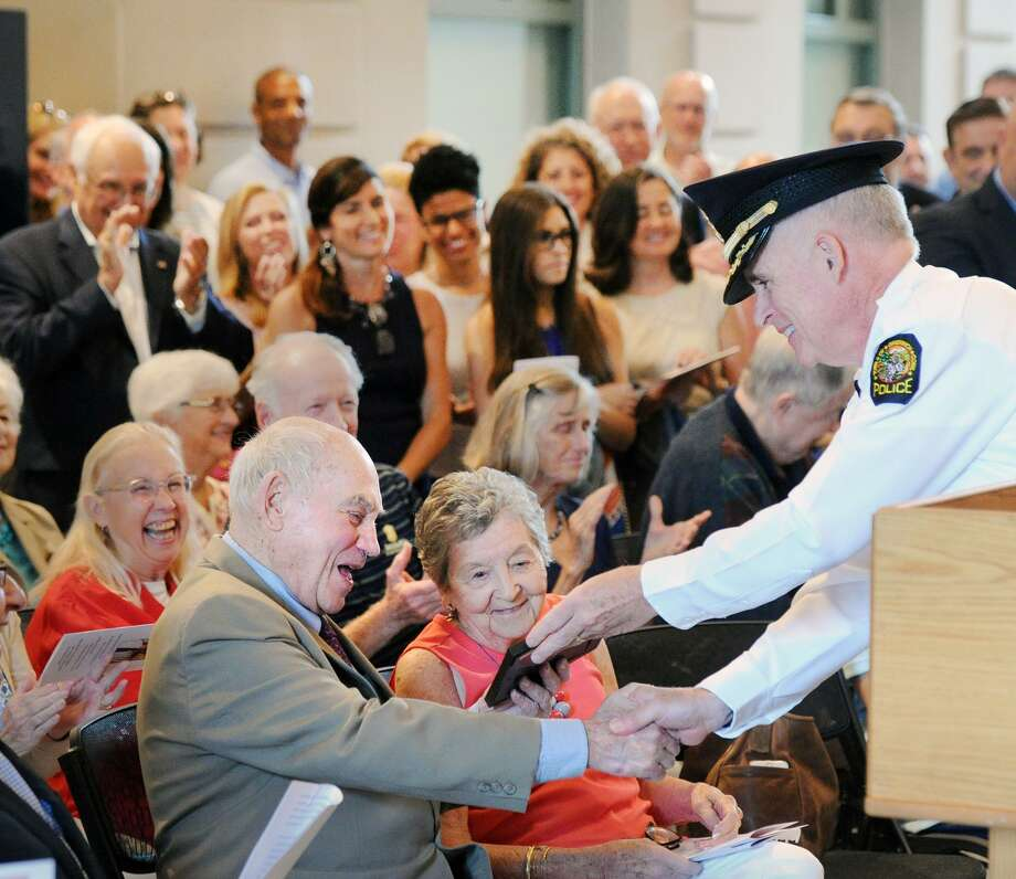 With his wife Dolly, center, looking on, John Margenot smiles as Greenwich Police Chief Jim Heavey gives Margenot a photo of when Margenot, serving as Greenwich First Selectman, swore Heavey in as a police officer during a ceremony and dedication of the John Margenot Atrium in his honor at the Public Safety Complex in Greenwich, Conn., Saturday, Sept. 8, 2018. Margenot, a former long-serving Greenwich First Selectman is now 90 years-old and still works as a town volunteer. Photo: Bob Luckey Jr. / Hearst Connecticut Media / Greenwich Time