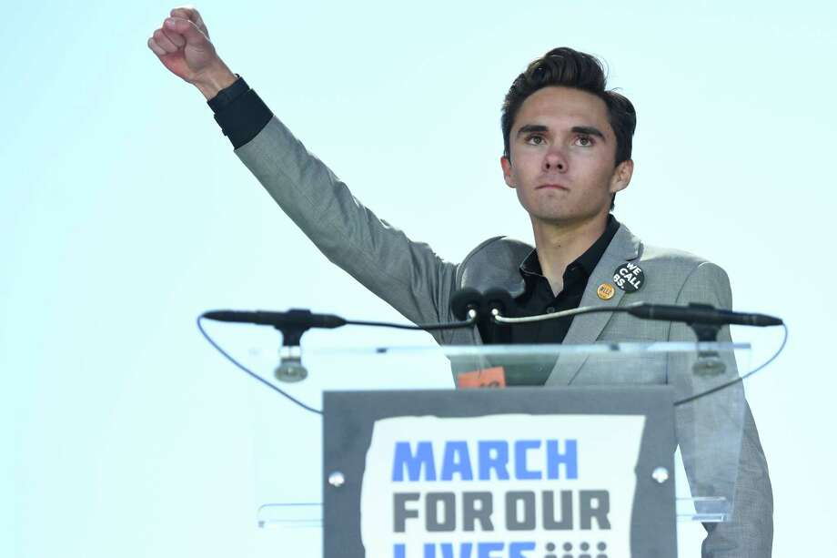 "(FILES) In this file photo taken on March 24, 2018 Marjory Stoneman Douglas High School student David Hogg speaks to the crowd during the March For Our Lives rally against gun violence in Washington, DC. A brother and sister who survived a shooting rampage at a Florida high school in February are writing a book about the campaign for stricter gun control in America sparked by the massacre, publisher Penguin Random House has announced.David and Lauren Hogg, who have become two of the most outspoken and media-friendly survivors of the Valentine's Day shooting that left 14 students and three staff dead at Marjory Stoneman Douglas High School in the city of Parkland.The book -- titled ""#NeverAgain"" in a reference to their movement -- will be released on June 5, 2018.David, who is 18, and younger sister Lauren, along with some of their classmates, launched the #NeverAgain movement, which saw hundreds of thousands of people take to the streets of US cities on March 24 for the ""March for Our Lives.""  / AFP PHOTO / JIM WATSONJIM WATSON/AFP/Getty Images Photo: JIM WATSON / AFP or licensors"
