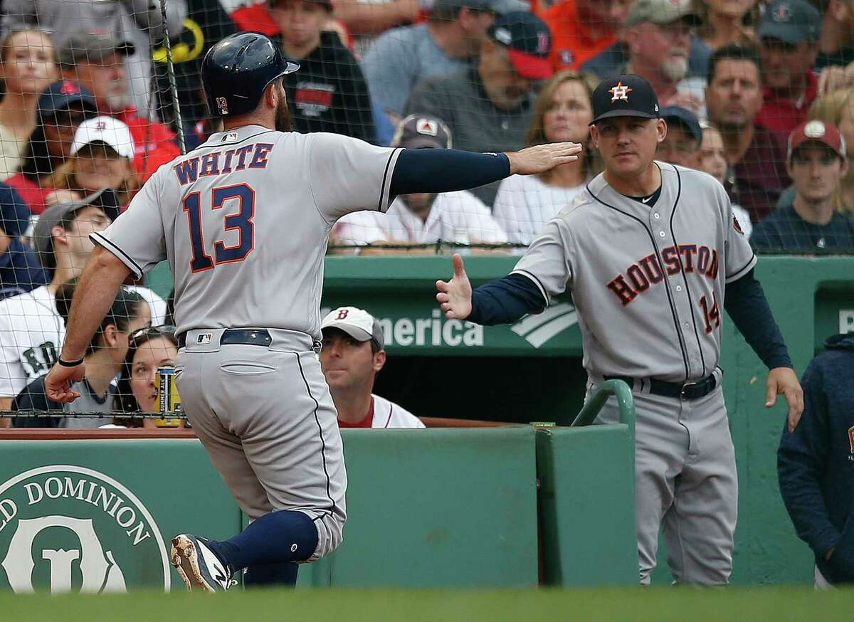 Houston Astros' Tyler White (13) celebrates with manager AJ Hinch (14) after scoring on a sacrifice fly by Jake Marisnick during the second inning of a baseball game against the Boston Red Sox in Boston, Saturday, Sept. 8, 2018. (AP Photo/Michael Dwyer)