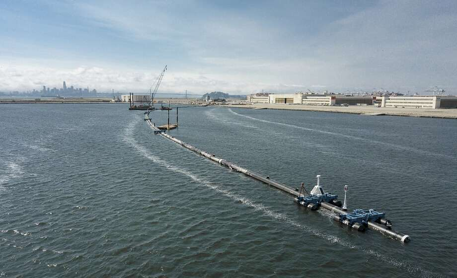 The Ocean Cleanup, a long floating boom that will be used to corral plastic litter in the Pacific Ocean is assembled in August 2018 in Alameda, Calif. Engineers will deploy the trash collection device to corral plastic litter floating between California and Hawaii in an attempt to clean up the world's largest garbage patch.  Photo: Associated Press