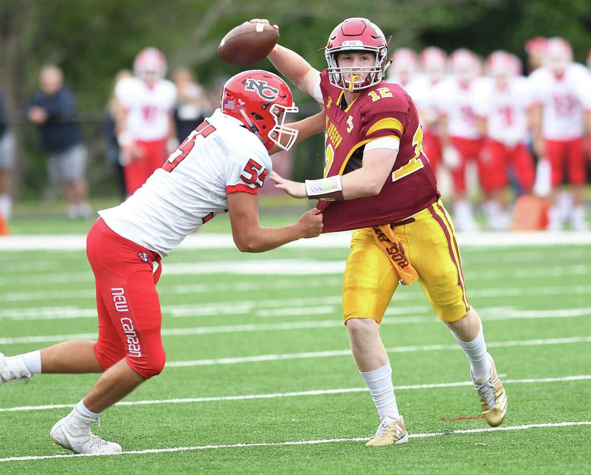 St. Joseph quarterback David Summers looks for the throw despite pressure from New Canaan's Harrison Skyrm.