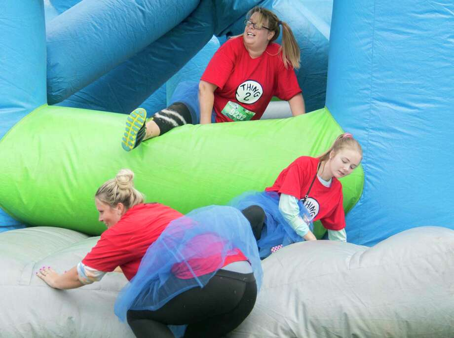 A group of runners spill through one of the bounce obstacles on the 2018 Insane Inflatable 5K Run at Ellms Family Farm in Ballston Spa, N.Y., on Saturday, Sept. 8. (Jenn March, Special to the Times Union) Photo: Jenn March / © Jenn March 2018 © Albany Times Union 2018
