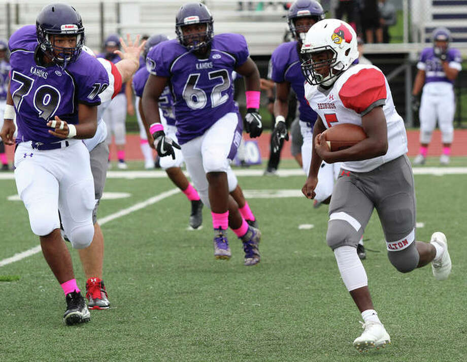 Alton running back Tim Johnson (right) beats Collinsville's Chris Garcia-Cloud (79) and Cole Hellman to the edge for some of his 233-yards rushing in the Redbirds' 35-6 Southwestern Conference victory Saturday at Collinsville. Photo: Greg Shashack / The Telegraph