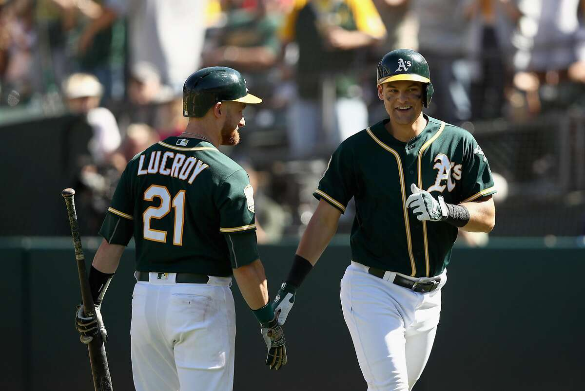 OAKLAND, CA - SEPTEMBER 08: Chad Pinder #18 of the Oakland Athletics is congratulated by Jonathan Lucroy #21 after he hit a home run in the sixth inning against the Texas Rangers at Oakland Alameda Coliseum on September 8, 2018 in Oakland, California. (Photo by Ezra Shaw/Getty Images)