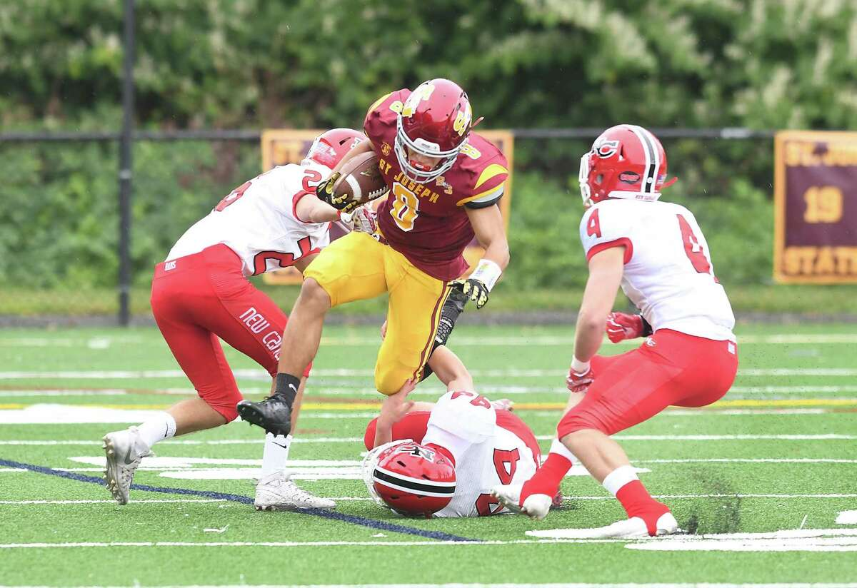 St. Joseph's Darren Warren (8) makes it through a trio of New Canaan defenders, from left, Stephen Golia, Christian Sibbett and Drew Guida during the St. Joseph football game, Sept. 8, 2018.