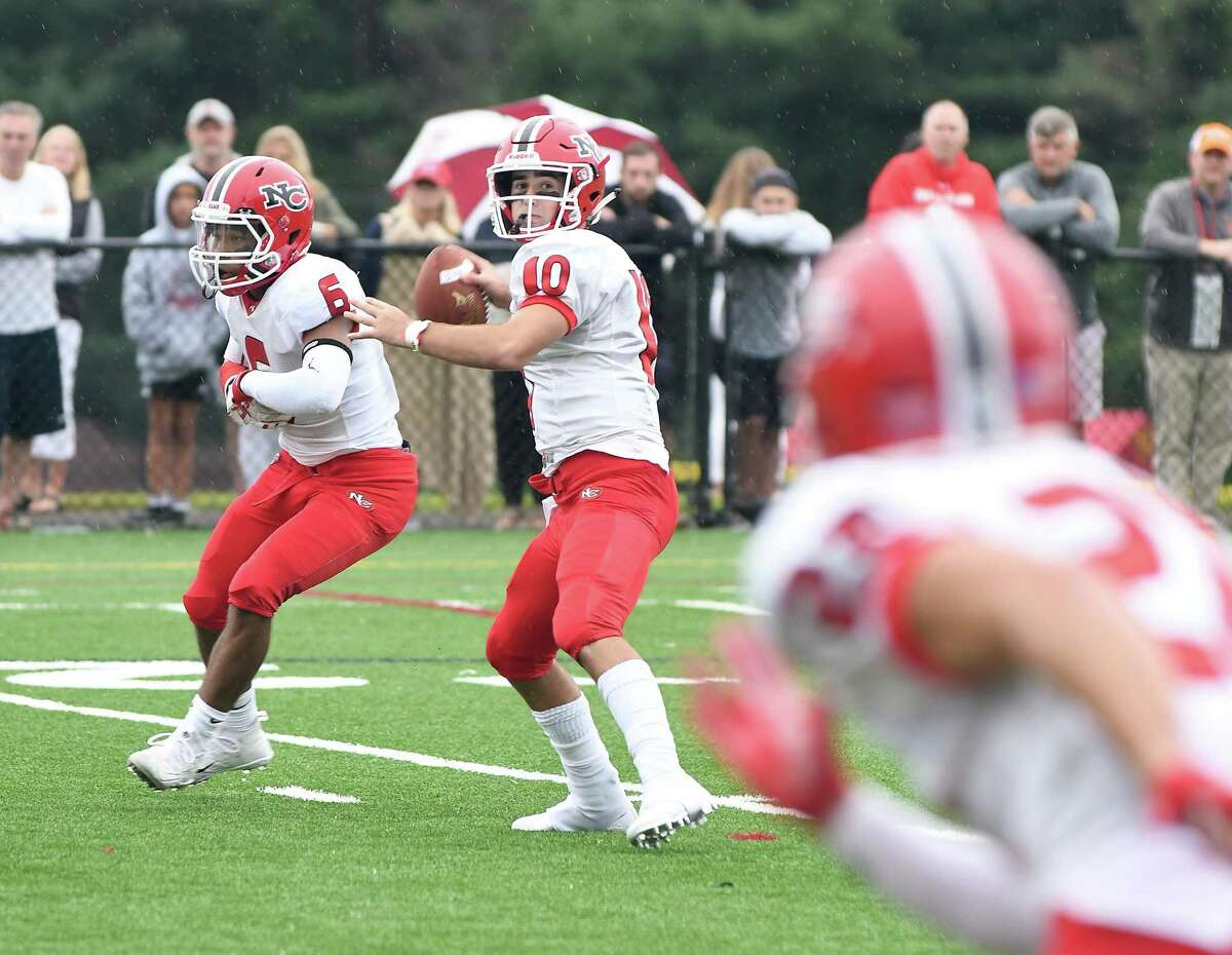 New Canaan's Drew Pyne looks for the pass during the New Canaan at St. Joseph's football game, Sept. 8, 2018. At left is teammate Wyatt Wilson.