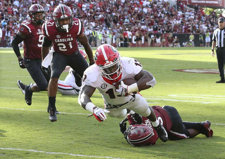 Georgia running back Elijah Holyfield breaks the tackle of South Carolina linebacker T.J. Brunson and dives into the endzone for a touchdown in the second half. Photo: Curtis Compton / Associated Press