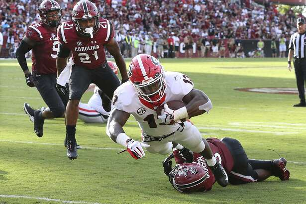 Georgia running back Elijah Holyfield breaks the tackle of South Carolina linebacker T.J. Brunson and dives into the endzone for a touchdown in the second half of an NCAA college football game, Saturday, Sept. 8, 2018, in Columbia, S.C. (Curtis Compton/Atlanta Journal-Constitution via AP)