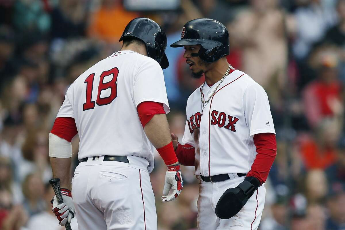 Boston Red Sox's Mookie Betts talks with Mitch Moreland (18) after scoring on a single by Xander Bogaerts during the first inning of a baseball game against the Houston Astros in Boston, Saturday, Sept. 8, 2018. (AP Photo/Michael Dwyer)