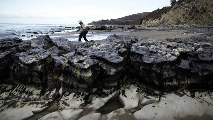 FILE - In this May 21, 2015 file photo, David Ledig, a national monument manager from the Bureau of Land Management, walks past rocks covered in oil at Refugio State Beach, north of Goleta, Calif. A California jury has found a pipeline company guilty of nine criminal charges for causing the 2015 oil spill that was the state's worst coastal spill in 25 years. The jury reached its verdict against Plains All American Pipeline of Houston on Friday, Sept. 7, 2018, following a four-month trial. (AP Photo/Jae Hong, File)