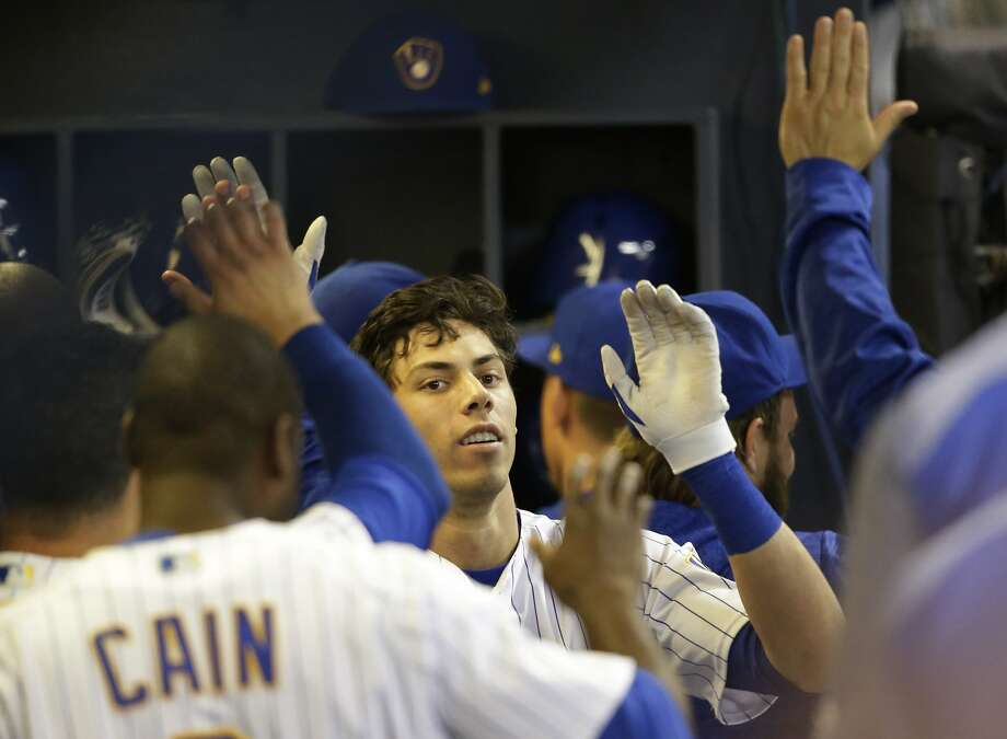 Milwaukee Brewers' Christian Yelich gets high-fives in the dugout after his home run against the San Francisco Giants during the fifth inning of a baseball game, Saturday, Sept. 8, 2018, in Milwaukee. (AP Photo/Jeffrey Phelps) Photo: Jeffrey Phelps / Associated Press