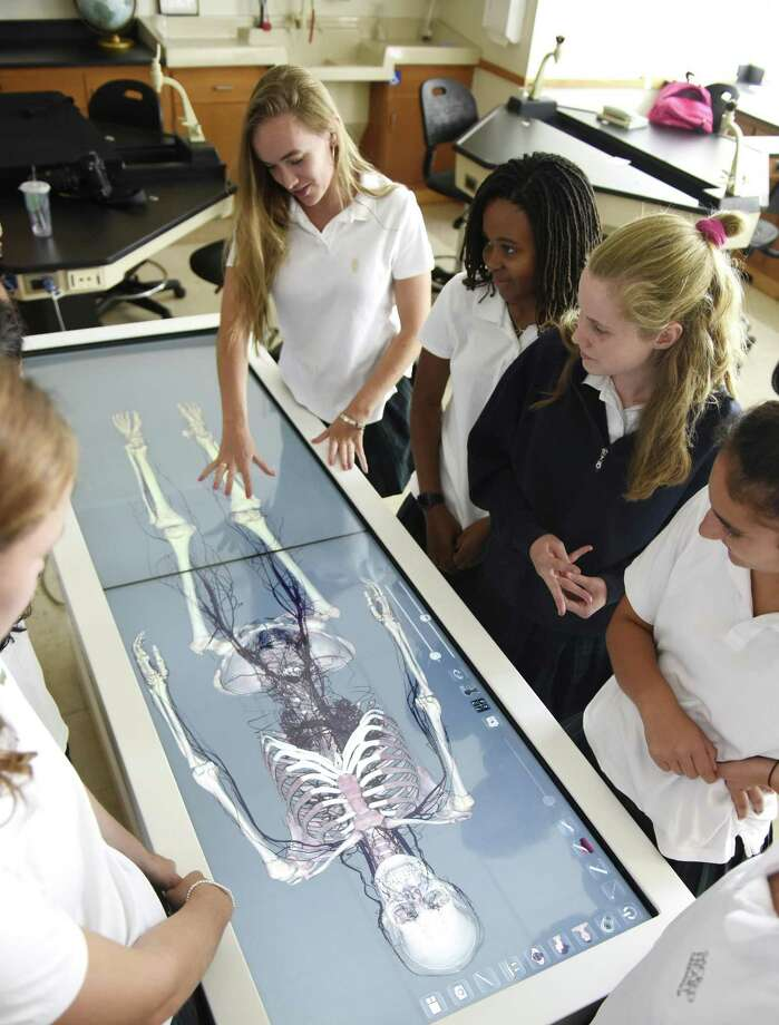 Upperclassmen, from left, Erin Quigley, Nia Foster, Meredith Wilson and Olivia Wise gather around the new virtual dissection table to see isolated layers and systems of the human body at Sacred Heart Greenwich in Greenwich, Conn. Thursday, Sept. 6, 2018. The Anatomage table allows students and teachers to dissect a virtual cadaver and explore anatomical features in 3D detail. Photo: Tyler Sizemore / Hearst Connecticut Media / Greenwich Time