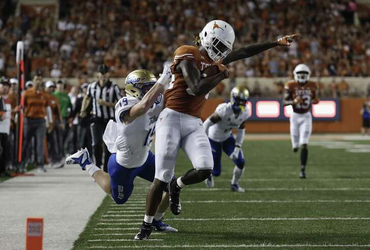 AUSTIN, TX - SEPTEMBER 08: Lil'Jordan Humphrey #84 of the Texas Longhorns shakes the tackle by Grant Sawyer #19 of the Tulsa Golden Hurricane and scores a touchdown in the second quarter at Darrell K Royal-Texas Memorial Stadium on September 8, 2018 in Austin, Texas. (Photo by Tim Warner/Getty Images)